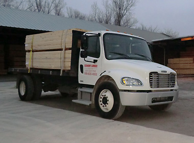 Image of a fully-loaded Economy Lumber Company delivery truck